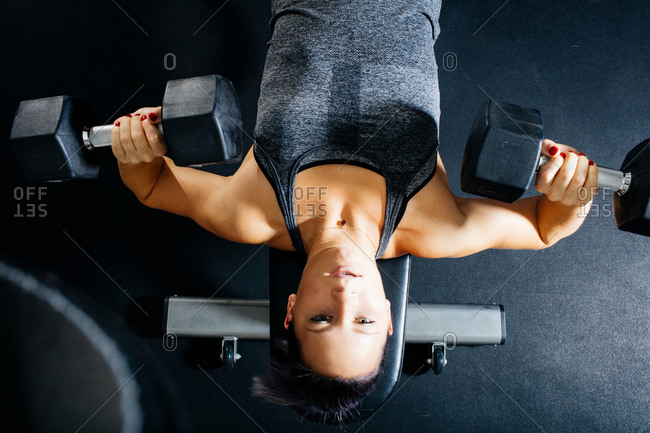 Overhead view of woman lying on back weight lifting