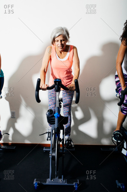 Women in gym using exercise bikes in spinning class