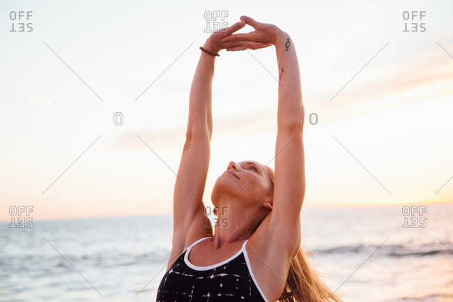 Woman on beach arms raised doing stretching exercise
