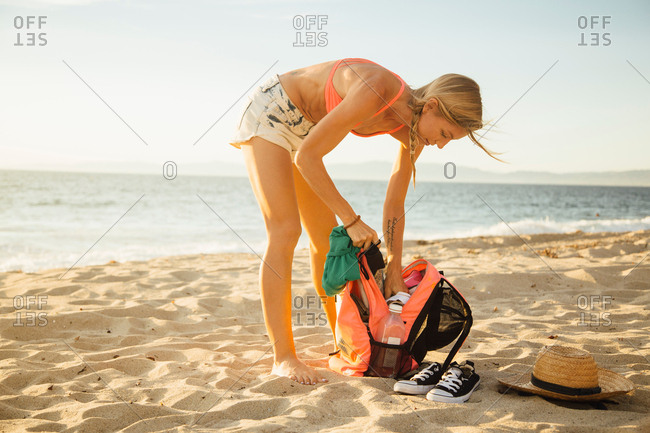 Woman on beach searching in back pack