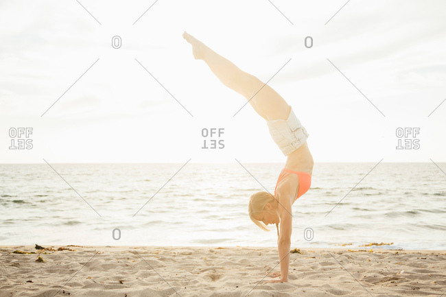 Woman on beach doing handstand