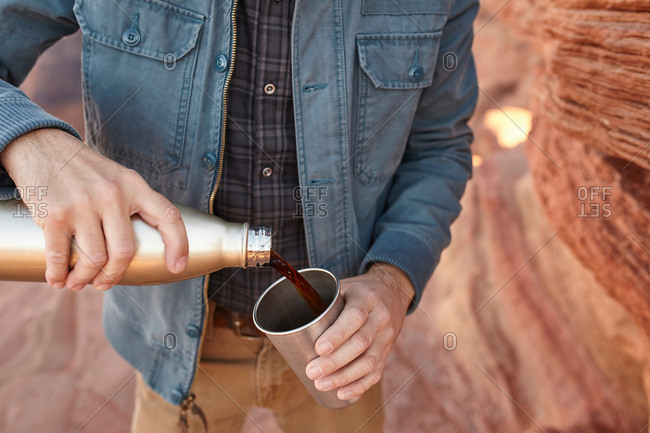 Man pouring hot drink from drinking flask, mid section, Page, Arizona, USA