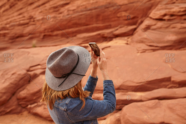 Woman taking photograph, using smartphone, Page, Arizona, USA