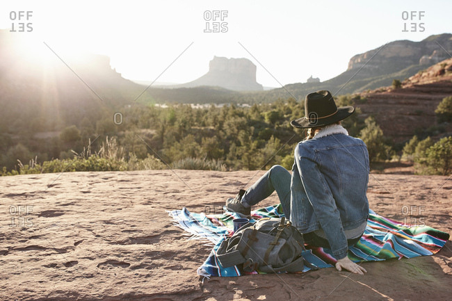 Woman sitting on blanket in desert, looking at view, rear view, Sedona, Arizona, USA