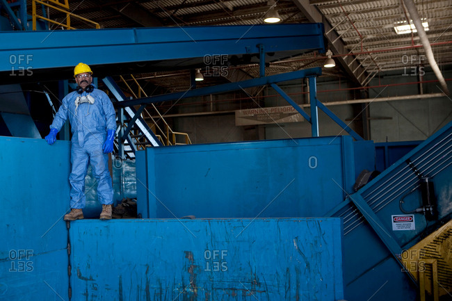 Portrait of male worker in hard hat standing on blue heavy machinery at recycling plant
