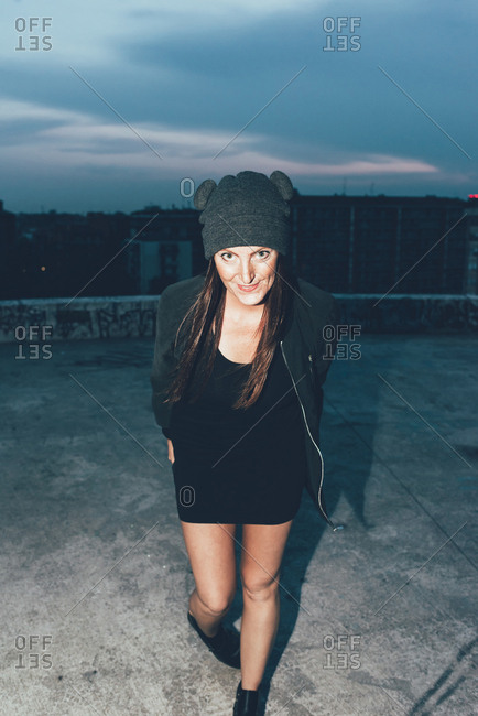 Portrait of young woman in knit hat on roof terrace above city at night