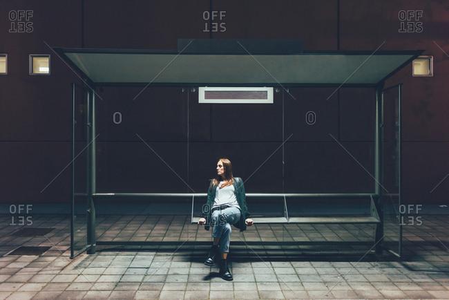 Young woman sitting at bus stop at night