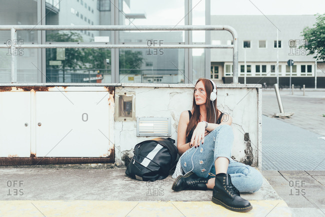 Young woman sitting outside office building listening to headphones