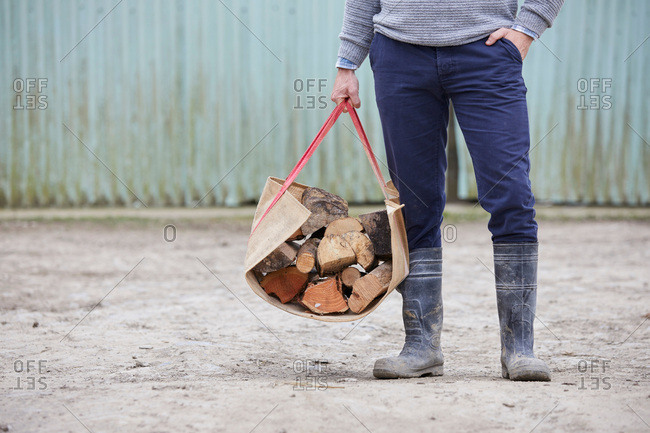 Waist down of man holding logs in log carrier