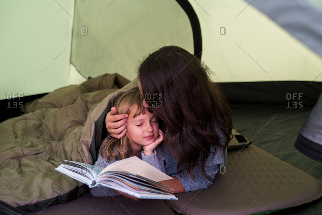 Mother and daughter in sleeping bag in tent, mother holding book