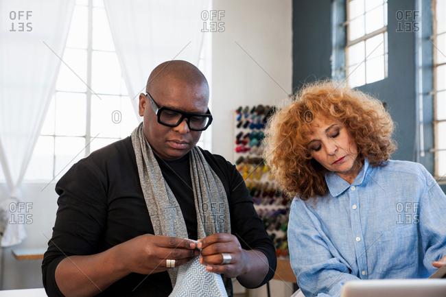 Male fashion designer examining material in design studio