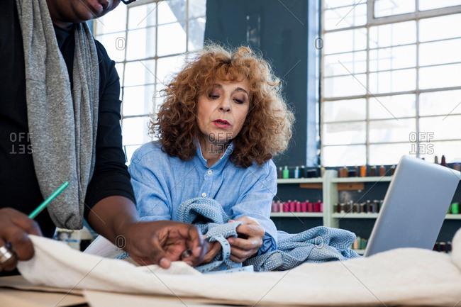 Male and female fashion designers examining material in design studio
