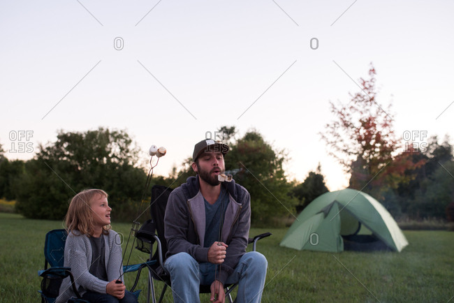 Father and daughter in camping chairs, eating toasted marshmallows