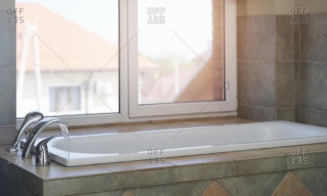 Bath with flowing water in domestic bathroom