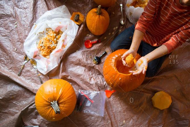 Boy scooping out pumpkin innards