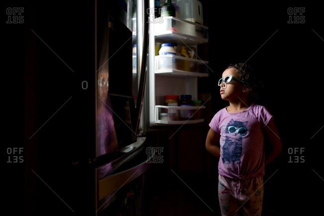 Girl in sunglasses reflected in fridge