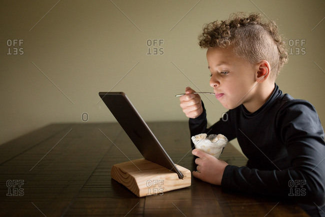 Boy eating snack watching tablet