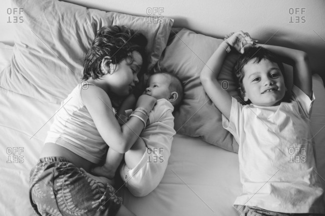 Baby lying with siblings on a bed