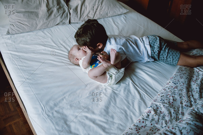 Boy and baby bonding on bed