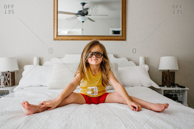 Boy in sunglasses sitting on bed
