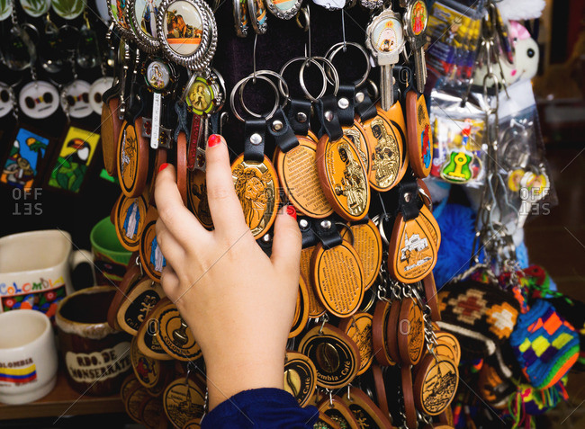 Hand grabbing keychains at market, Colombia