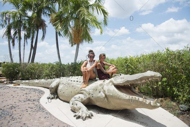 Darwin, Australia - December 4, 2015: Tourists on a crocodile sculpture