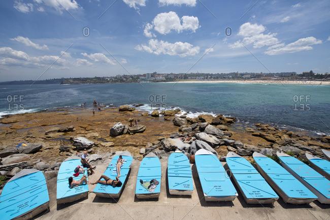 Sydney, Australia - December 11, 2015: People lounging on boats, Bondi Beach