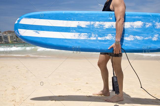 Man with a surfboard on Bondi Beach