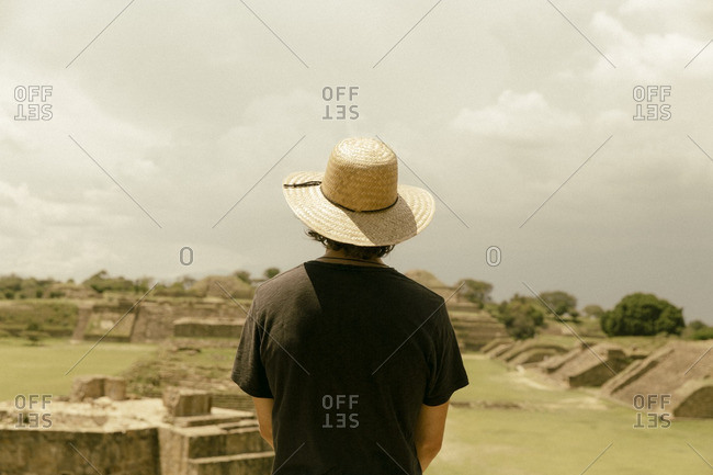 Man looking at ruins in Oaxaca, Mexico