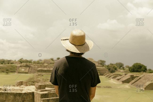 Man looking at ruins in Oaxaca, Mexico