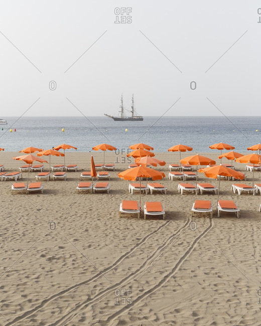 Spain, Isle of Tenerife. A beach at Los Cristiano's with beach beds, umbrella's and a sail boat in front of the coast.
