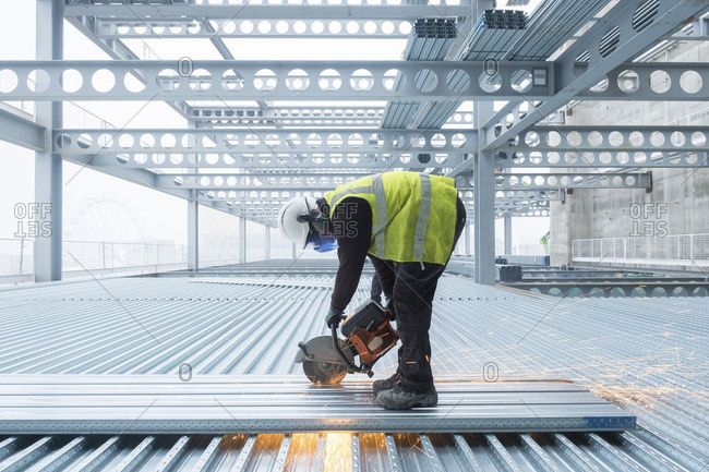 Workman cutting steel flooring on a building site in full protective clothing