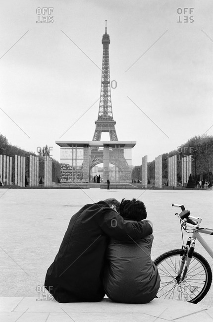 Parisian couple holding each other by the Eiffel Tower in Paris France