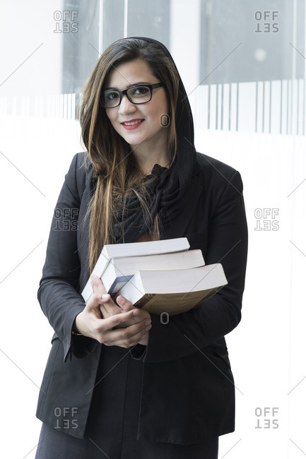 Female student with text books in a university setting.
