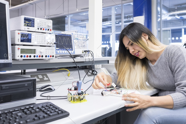 A female electronics student studying in an electronics engineering lab.