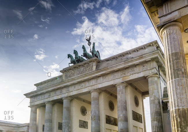 Brandenburg Gate with backlight, blue sky with fluffy clouds