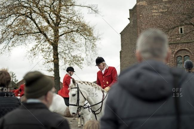 Geesteren, Achterhoek, Gelderland, The Netherlands - November 19, 2016: Horse riders gather at church of village at start of drag hunting.