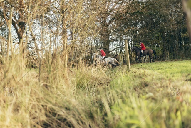 Geesteren, Achterhoek, Gelderland, The Netherlands - November 19, 2016: Men on horses jumping over ditch in field for drag hunting.
