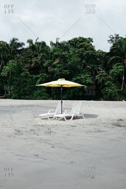 Two white beach chairs in the sand with yellow umbrella