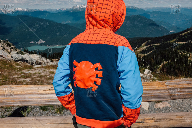 Whistler, Canada - August 25, 2016: Boy wearing a spiderman costume looking over the mountains
