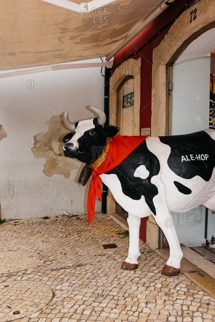 Lisbon, Portugal - November 11, 2016: A plastic cow stands in the entrance of a shop