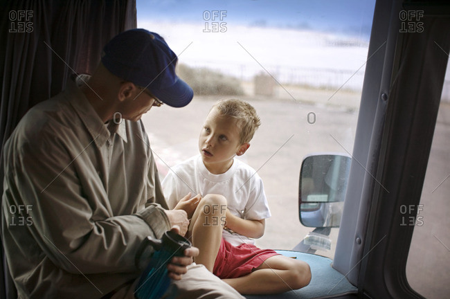 Grandfather and grandson talking together in their camper van.