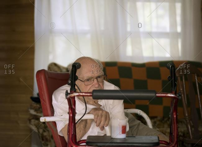Elderly man sitting in his living room.
