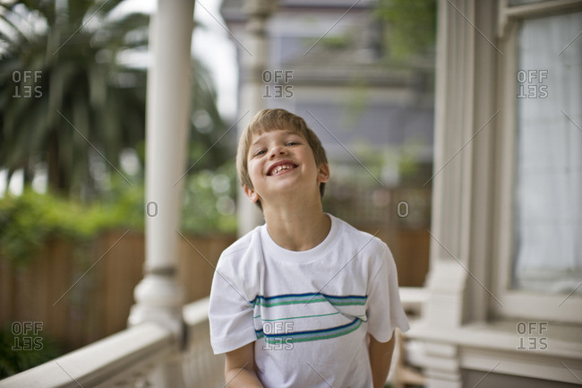Smiling young boy on the porch of his house.