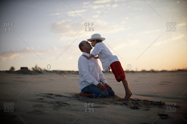 Father and son sharing a kiss on the beach.