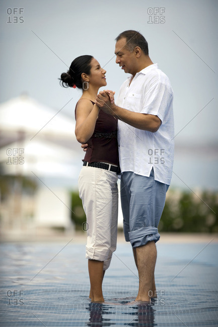 Couple dancing together in a resort infinity pool.