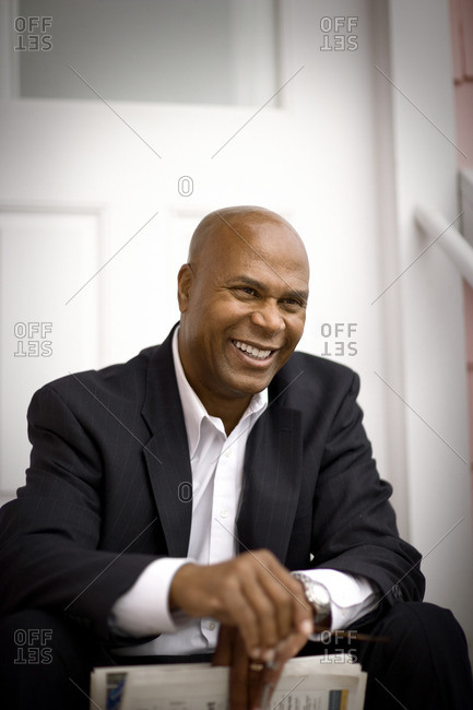 Smiling businessman sitting on his doorstep.