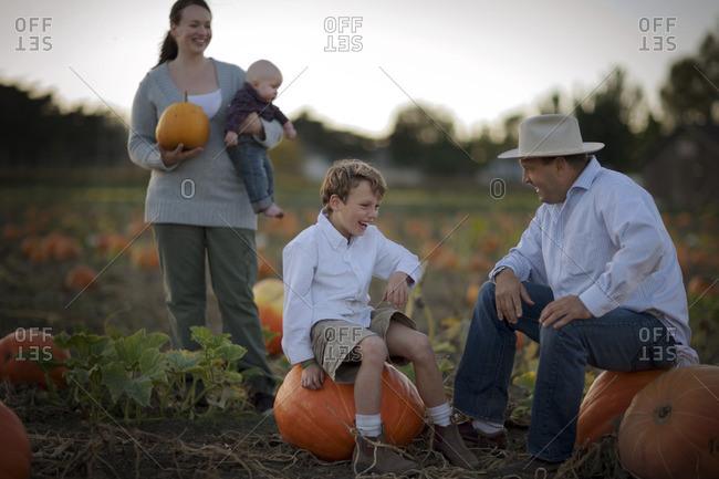 Family choosing a Halloween pumpkin at a pumpkin patch.