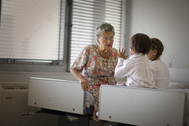 Senior woman being visited in hospital by her two young grandchildren.