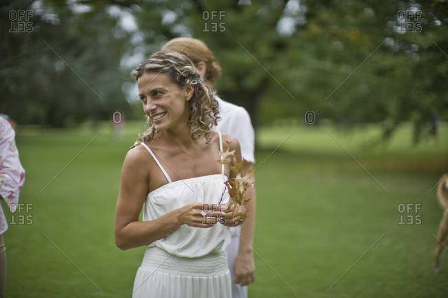 Smiling woman in a white dress holding an autumn leaf.